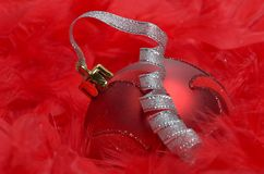 Christmas ball over red feathers Royalty Free Stock Image