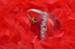 Christmas ball over red feathers Stock Photo