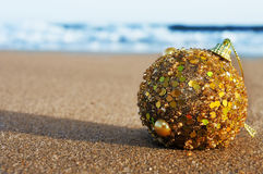 Christmas ball on the sand of a beach. A golden christmas ball on the sand of a beach stock images