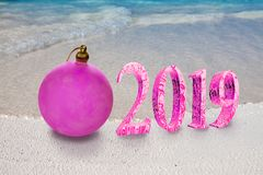 Christmas ball on the sandy seashore and the inscription 2019- New Year`s card royalty free stock photos