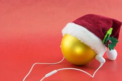 Christmas ball with Santa's hat and earphones Royalty Free Stock Images