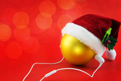 Christmas ball with Santa's hat and earphones, on red Stock Photo