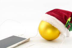 Christmas ball with Santa's hat and earphones Royalty Free Stock Photo