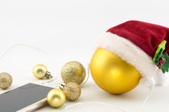 Christmas ball with Santa's hat and earphones Royalty Free Stock Image