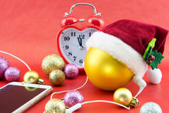 Christmas ball with Santa's hat, smartphone with earphones Stock Image