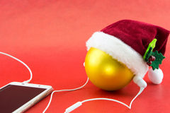 Christmas ball with Santa's hat and smartphone with earphones Stock Photos