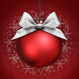 Christmas ball with silver satin ribbon bow on red Stock Photo