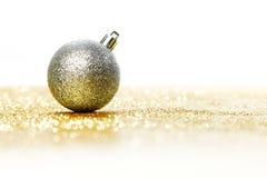 Christmas ball. Silver christmas ball on shiny golden background Stock Photography