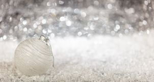 Christmas ball and snow, abstract bokeh lights background, copy space. Banner stock photography
