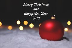Christmas ball on snow and greeting message against blurred background. Winter holidays royalty free stock image