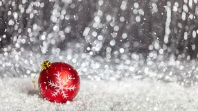 Christmas ball and snow in the night, abstract bokeh lights background. Copy space royalty free stock image