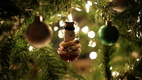 Christmas ball, snowman garland decoration on Christmas tree with bokeh lights.  stock video footage