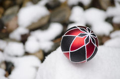 Christmas ball on snowy rock Stock Images