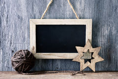Christmas ball and star, and blank chalkboard. A wooden-framed chalkboard with a blank space, a handmade christmas ball and a wooden christmas star, on a rustic stock photo