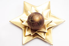 Christmas ball on star shaped plate Royalty Free Stock Images