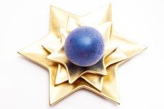 Christmas ball on star shaped plate Stock Photos