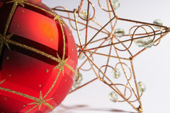 Christmas ball with star - weinachtskugel mit stern. Red christmas tree ball with decoration and a golden star in the background - rote Weihnachtskugel mit Royalty Free Stock Image