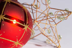 Christmas ball with star - weinachtskugel mit stern. Red christmas tree ball with decoration and a golden star in the background - rote Weihnachtskugel mit Royalty Free Stock Photography