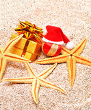 Christmas ball, starfishes and a gift box on  sand Royalty Free Stock Image