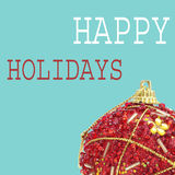 Christmas ball and text happy holidays, in a pop art style. An ornamented red christmas ball and the text happy holidays on a blue background, in a pop art style royalty free stock photo