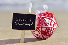 Christmas ball and text seasons greetings on the beach. A chalkboard with the text seasons greetings and a handmade christmas ball, made with different ribbons Stock Photos