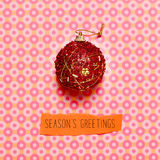 Christmas ball and text seasons greetings on a colorful backgrou. A red christmas ball and the text seasons greetings on a colorful circles-patterned background Stock Photo