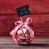 Christmas ball and text seasons greetings. A handmade christmas ball, made with different ribbons and buttons, topped with a flag-shaped signboard with the text Stock Image