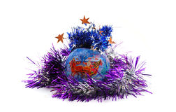 Christmas ball with tinsel. Blue Christmas ball with purple tinsel isolated on white Royalty Free Stock Image