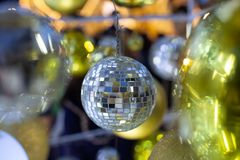 Christmas disco ball on a blurred festive background in time for new year holiday. Christmas ball on a tree on blurred background royalty free stock image