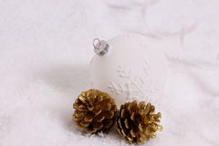 Christmas ball, two gold pine cones in snow Stock Image