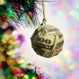 Christmas ball wrapped in a banknote Stock Photos