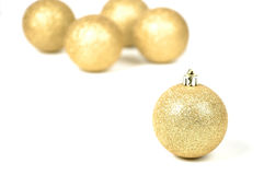 Christmas balls. Four golden christmas balls in the background, one sharp in the foregrand Royalty Free Stock Photography