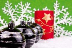 Christmas balls. Black christmas balls wtih candle on snow Stock Image
