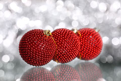 Christmas balls. Red Christmas balls on silver blurred background royalty free stock photography
