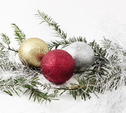Christmas balls. Three Christmas balls sourrounded by branches and some silver christmas decoration Royalty Free Stock Images