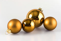Christmas balls. 4 golden christmas balls with a white backround royalty free stock image