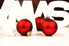 Christmas balls. XMAS letters with Christmas tree ornaments Royalty Free Stock Image