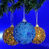 Christmas balls. Some golden and blue christmas balls hanging of a christmas tree on a blue background stock image