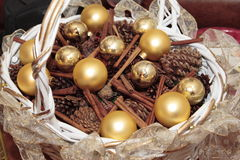 Christmas Balls. Shiny Gold Christmas balls and holiday decorations in a basket Stock Photo
