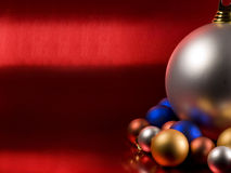 Christmas balls. On a metallic red background Royalty Free Stock Photography
