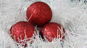Christmas balls. Three red sparkly chrismtas balls on tinsel Stock Photo