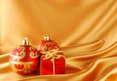 Christmas balls. Two christmas balls and gift on the gold background royalty free stock images