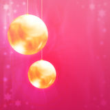 Christmas balls. Golden Christmas balls on a pink background Stock Images