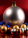 Christmas Balls. On a metallic red background Stock Photos