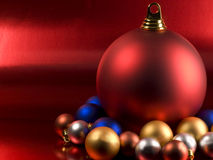 Christmas Balls. On a metallic red background Royalty Free Stock Photos