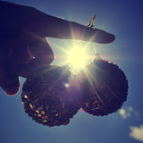 Christmas balls in afinger with a sunbeam and backlighted, with. Christmas balls hanging in the forefinger of a young man with a sunbeam and backlighted, with a Royalty Free Stock Photos