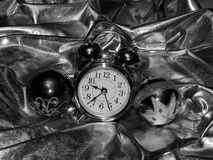 Christmas balls with an alarm clock on a black and white image royalty free stock image
