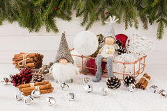 Christmas balls in basket, gnome and angel, Christmas tree on white wooden background Stock Photo