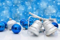 Christmas Balls and Bells. Blue christmas balls and bells on a blue sparkle background, christmas time Stock Photo