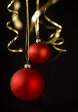 Christmas balls on black. Red christmas balls and golden ribbons isolated on black Royalty Free Stock Photography